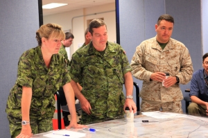 Maj. Lisa Hampson (left), intelligence officer with the 33 Canadian Brigade Group, Maj. Stephen Young (center), armor officer with 33 CBG, and Maj. Mark Paolicelli (right), operations officer with 1st Air Naval Gunfire Liaison Company, participate in a brief during Javelin Thrust 2012/Large Scale Exercise-1 at Camp Pendleton, Calif., July 10. Javelin Thrust 2012/Large Scale Exercise-1 was conducted at the Marine Corps Air Ground Combat Center in Twentynine Palms, Calif. More than 5,000 Marines from the 1st Marine Expeditionary Brigade, part of I MEF and Marine Forces Reserve, participated in the exercise. The exercise allowed Canadian and U.S. forces to work together and continue its longstanding relationship.